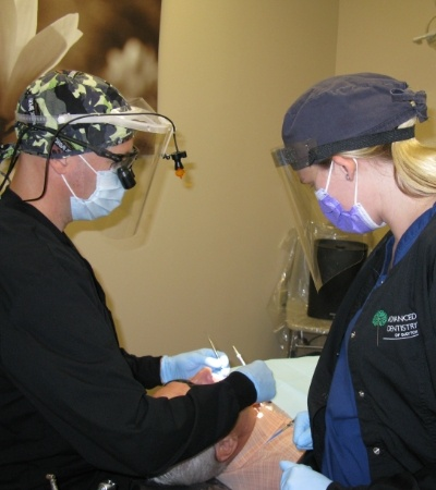 Dentist and team member providing dental implant supported replacement tooth