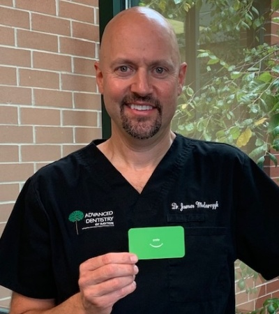 Dentist who provides dental implant tooth replacement holding up his card