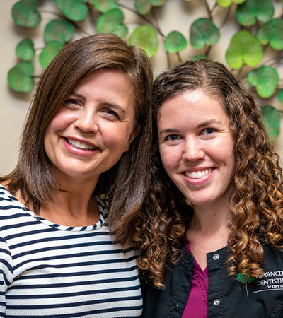 Two dental implant team members smiling